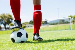 Fotbollsspelareanseende med hans fot på boll Fotografering för Bildbyråer