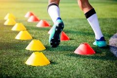 Fotbollsspelarejogga och hopp mellan kottemarkörer på grönt a fotografering för bildbyråer