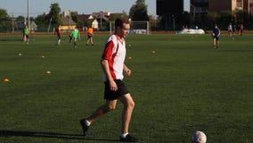 Fotbollsspelaren är utbilda och studsa en fotbollboll på hans ben lager videofilmer