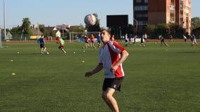 Fotbollsspelaren är utbilda och studsa en fotbollboll vid hans ben lager videofilmer