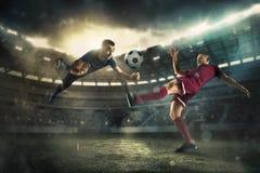 Fotbollsspelaren i rörelse på fältet av stadion Arkivfoto
