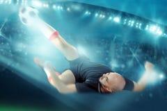 Fotbollsspelaren skjuter bollen in i den omvända porten Arkivfoto
