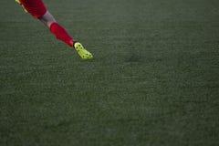 Fotbollsspelaren skjuter fotbollbollen på konstgjort torvafält Arkivfoto