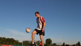 Fotbollsspelaren sparkar bollen med hans fot under utbildningen lager videofilmer
