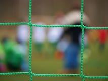Fotbollsspelaren står mot mål med netto och stadion Fotbollporten förtjänar Fotbollport royaltyfria foton