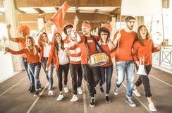 Fotbollsupportern fläktar vänner som hurrar och går till fotbollsmatchen royaltyfria foton