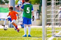 Fotbollutbildningslek för ungar Ung pojke som ett fotbollmålvaktanseende i ett mål Fotbollspelare som jagar bollen Royaltyfria Foton