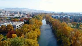 Fotbron korsar Boise River med nedgången färgade träd och staden arkivfilmer