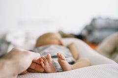 Foten av det nyfött behandla som ett barn att ligga in behandla som ett barn kokong, och händerna av hans fader klipps och att br Royaltyfri Foto