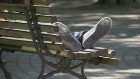 Foten av en person som sover i ett offentligt, parkerar