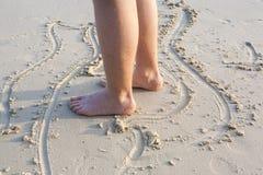 Foten av en pojke målar diagram i den fina sanden Fotografering för Bildbyråer