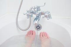 Foten av en ung kvinna i ett badkar arkivfoto