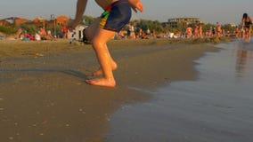 Foten av ett barn på ett hav sätter på land stock video
