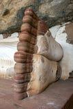 Foten av 48 fot den långa sova Buddhastatyn på den Pidurangala templet på Sigiriya i Sri Lanka Royaltyfri Fotografi