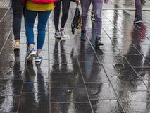 Foten av gångare reflekterade i den våta gråa trottoaren royaltyfria foton