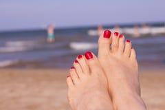 Foten av kvinnan med spikar målat rött på sanden av havet Fotografering för Bildbyråer
