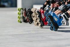 Foten av rollerbladers som bär inline rullskridskor som sitter i utomhus- skridsko, parkerar, stänger sig upp sikt av hjul, innan arkivbilder