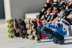 Foten av rollerbladers som bär inline rullskridskor som sitter i utomhus- skridsko, parkerar, stänger sig upp sikt av hjul, innan royaltyfria foton