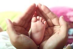 Foten för barn` s i händer för moder` s Royaltyfri Bild