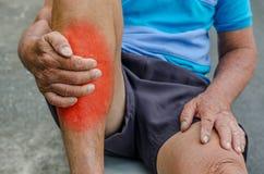 Foten för handen för den höga mannen smärtar den hållande och masseraankeln in område arkivbild