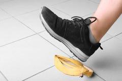 Foten för man` s i genomdränkta svarta instruktörer beträder på en gul peel från en saftig, smaklig organisk banan på bakgrunden  Royaltyfri Bild