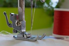Foten för symaskin` s med en visare syr ecrufärgtyg närbild Fotografering för Bildbyråer