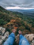 Foten hänger över kanten av en klippa som förbiser en dal som fylls med höstfärger royaltyfria bilder