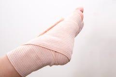 Foten med förbinder fotskadan som stukas foten, den stukade ankeln Arkivfoto