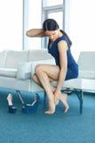 foten smärtar Den unga kvinnan masserar henne tröttade ben arkivbild