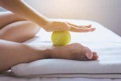 Foten sular massagen, kvinna som handen som ger massage med tennisbollen till henne, foots i sovrum fotografering för bildbyråer