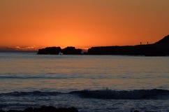 Fotgängare som tycker om solnedgången arkivbild