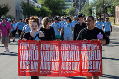 Fotgängare med tecknet på AIDSwalk Royaltyfri Foto