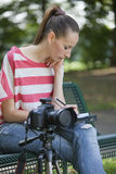 Fotógrafo de sexo femenino que hace el aviso Imagen de archivo libre de regalías