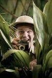 Fotógrafo del explorador que oculta en la vegetación Foto de archivo libre de regalías