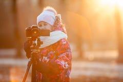 Fotógrafo del niño joven que toma imágenes en cámara usando el trípode, luz de la puesta del sol, copyspace Imagen de archivo libre de regalías