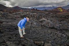 Fotógrafo joven en el fondo de rocas volcánicas Foto de archivo