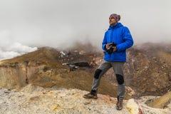 Fotógrafo joven en el fondo de rocas volcánicas Imágenes de archivo libres de regalías