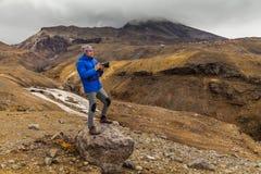 Fotógrafo joven en el fondo de rocas volcánicas Fotografía de archivo libre de regalías