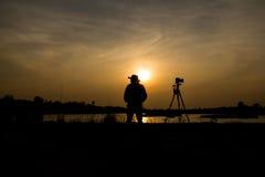 Fotógrafo un lago en puesta del sol Imagenes de archivo