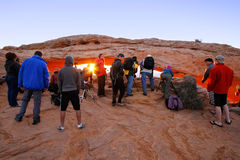 Fotógrafos y turistas que miran salida del sol en Mesa Arch, Canyo Foto de archivo