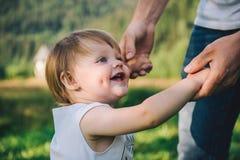 Fother tient ses mains de fille, aide sa promenade Image stock