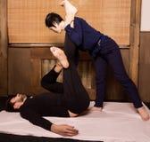 Fotmassage i thailändsk studio Yrkesmässig terapeut som ger traditionell thailändsk massage royaltyfri fotografi