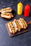 Foto överst av hotdogs på plattan och bräde med ketchup och senap Royaltyfri Fotografi