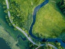 A foto aérea da estrada que vai pelo rio sob as árvores, cobre abaixo da vista na mola adiantada em Sunny Day imagens de stock royalty free