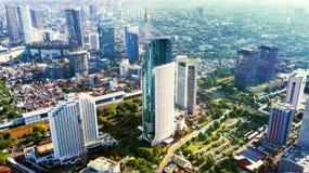 Foto aérea da torre icónica de BNI 46 com os prédios de escritórios situados no distrito financeiro central sul de Jakarta, imagem de stock