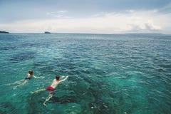 Foto aérea de pares jovenes el los días de fiesta que nadan en el océano Imágenes de archivo libres de regalías