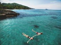 Foto aérea de pares jovenes el los días de fiesta que nadan en el océano Imagen de archivo libre de regalías