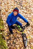 A foto aérea de um menino monta uma bicicleta no parque do outono fotografia de stock royalty free