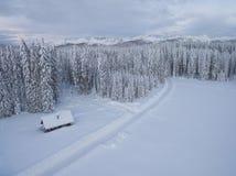 Foto aérea de una casa de madera al lado del bosque y montañas cubiertas en nieve detrás de ella en invierno frío fotos de archivo