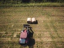 Foto aérea del abejón del granjero Harvesting Hay Rolls en el campo de trigo con un tractor rojo - Sunny Summer Day, apariencia v imágenes de archivo libres de regalías